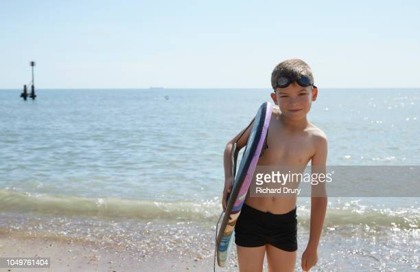 Portrait of a young boy at the beach holding his bodyboard