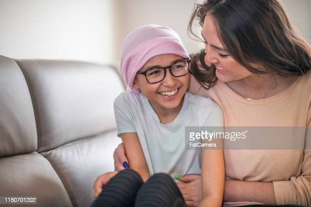 portrait of a young boy battling cancer as his mom embraces him - leukemia stock pictures, royalty-free photos & images