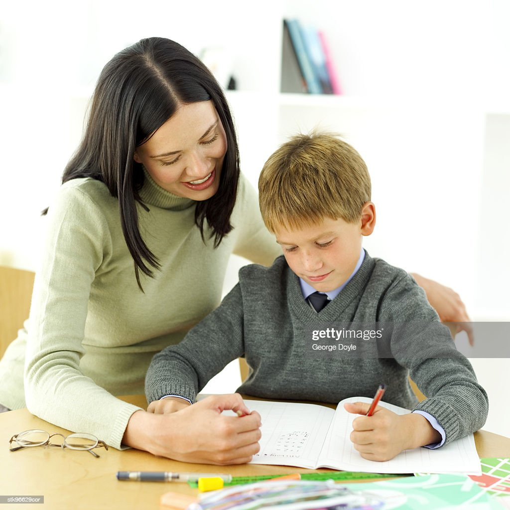 portrait of a young boy being tutored by his teacher : Stock Photo