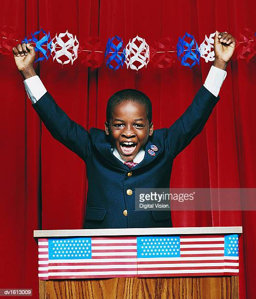 Portrait of a Young Boy Cheering and Standing on a Podium With His Arms up