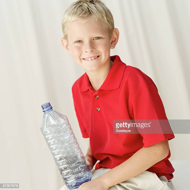 Portrait of a young boy (8-9) holding a bottle of water