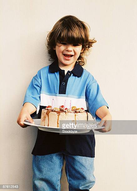 Portrait of a young boy (4-6) holding a cake on a plate