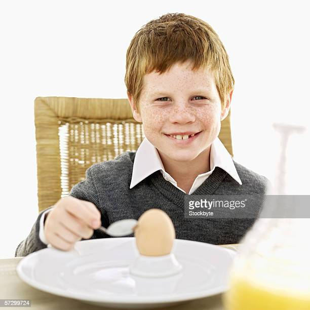 Portrait of a young boy (8-10) holding a spoon sitting in front of a plate with a hard boiled egg