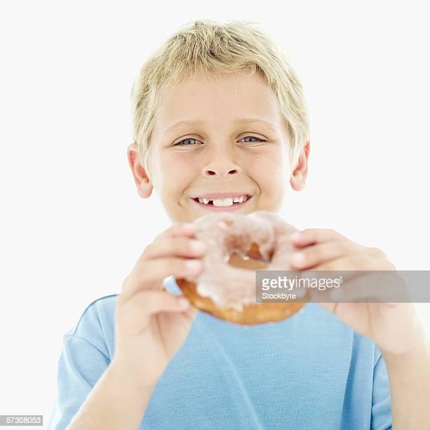 Portrait of a young boy (8-9) holding a sugar glazed doughnut
