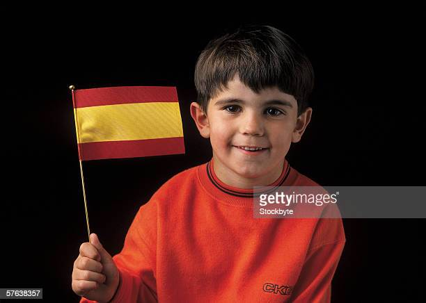 Portrait of a young boy (6-8) holding the flag of Spain