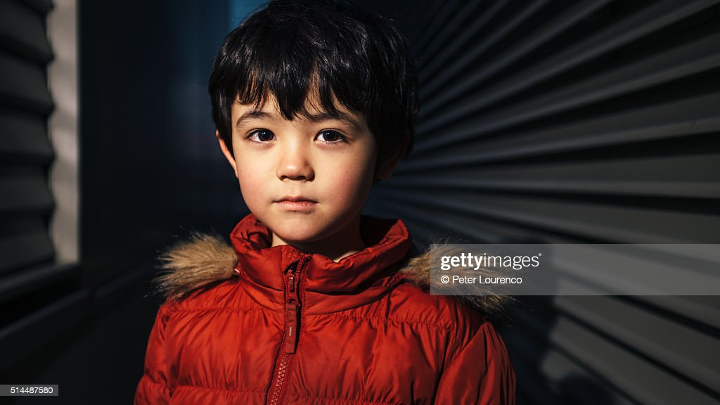 Portrait of a young boy in a dark space : Stock Photo