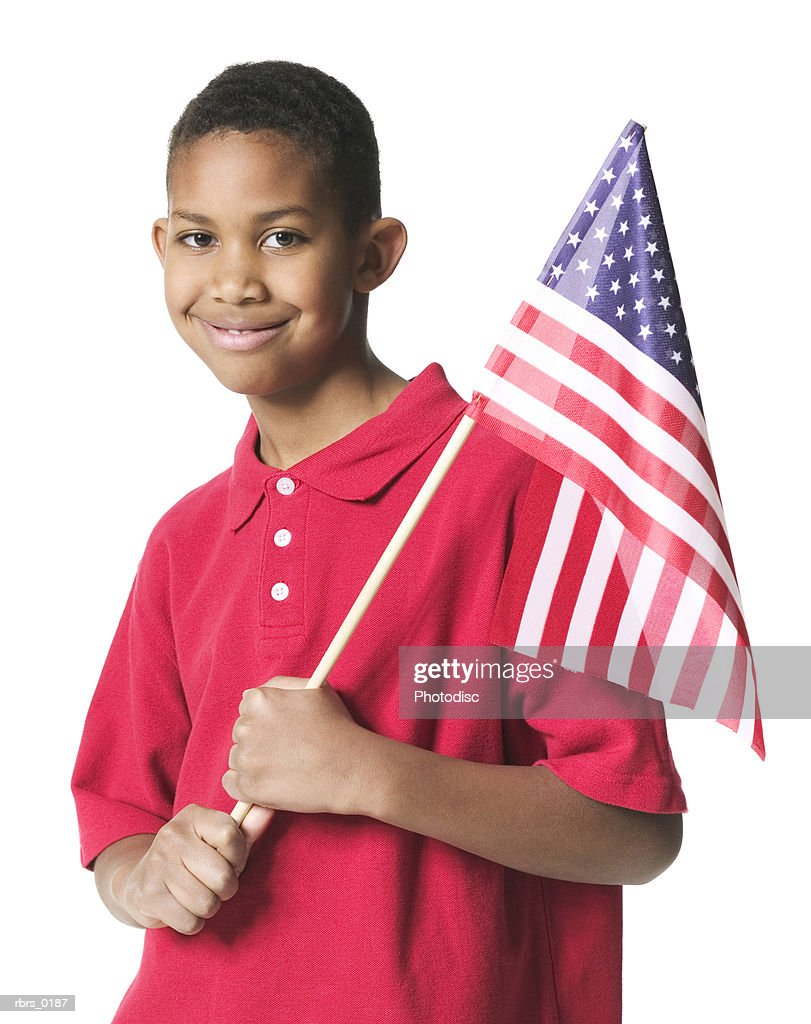 portrait of a young boy in a red shirt as he holds an american flag and smiles : Foto de stock
