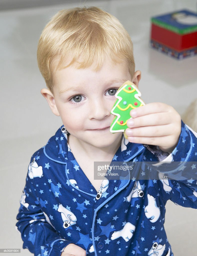 Portrait of a Young Boy in Pyjamas Holding a Christmas Tree Cookie : Stock Photo