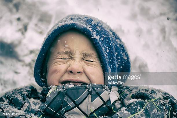 Portrait of a young boy in snow making a face