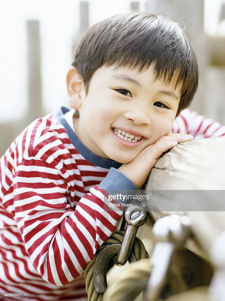 Portrait of a Young Boy Leaning Against a Wooden Post : Stock Photo