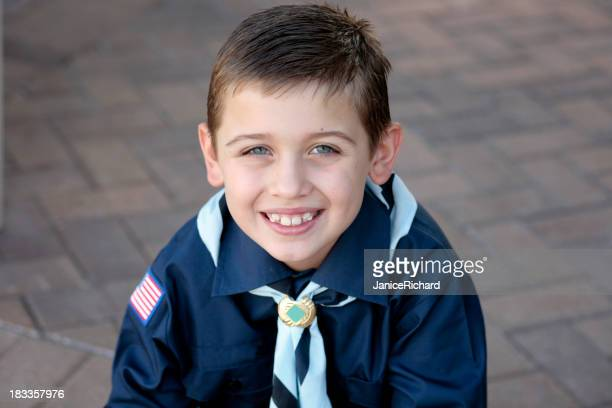 Portrait of a young boy scout in blue uniform smiling