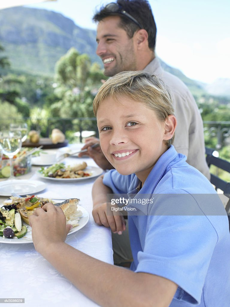 Portrait of a Young Boy Sitting at a Meal on a Table Outdoors : Stock Photo