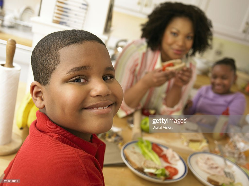 Portrait of a Young Boy Sitting at a Table for Lunch With His Family : Stock Photo