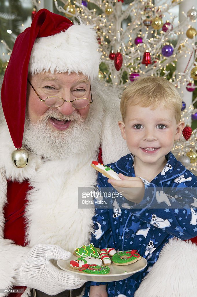 Portrait of a Young Boy Sitting on Father Christmas' Lap, Handing Him a Cookie : Stock Photo