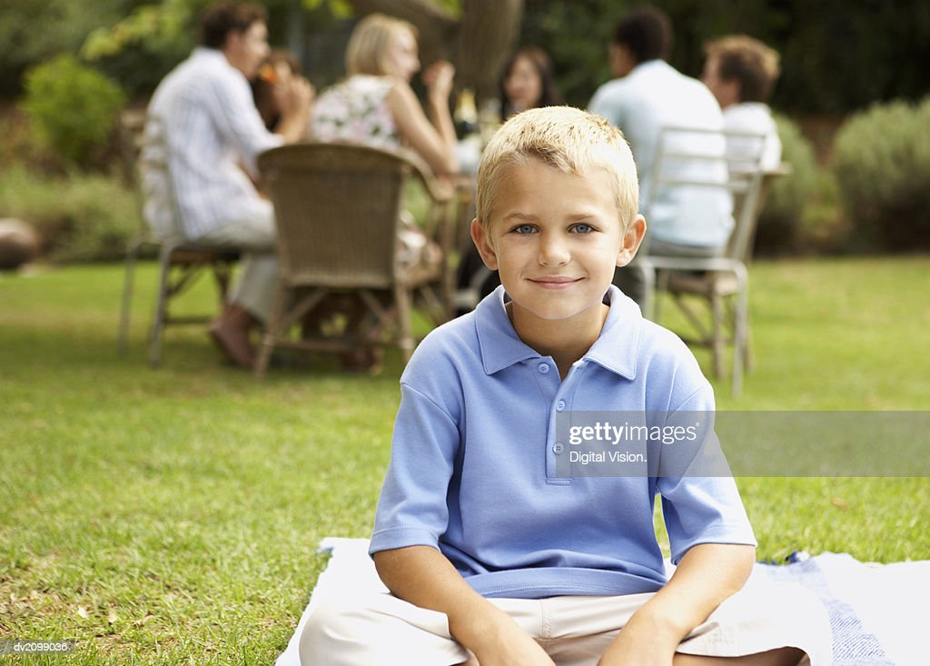 Portrait of a Young Boy Sitting on the Grass in the Garden, People at a Table in the Background : Stock Photo
