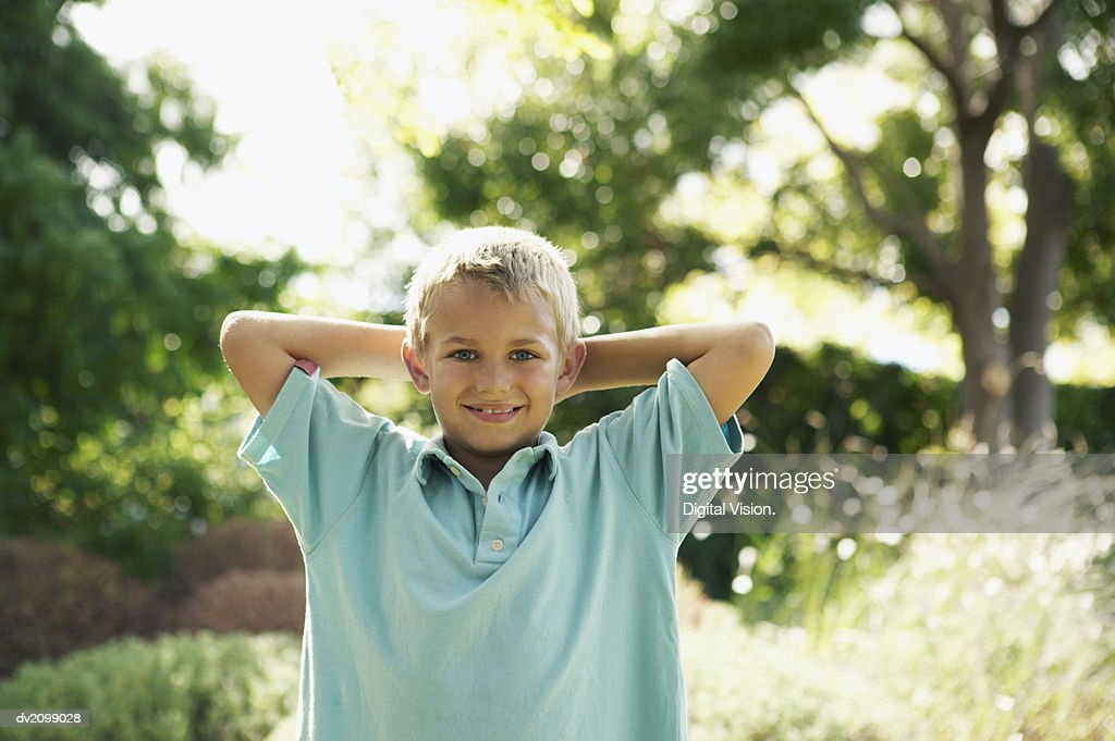 Portrait of a Young Boy Standing in a Garden With His Hands Behind His Head : Stock Photo