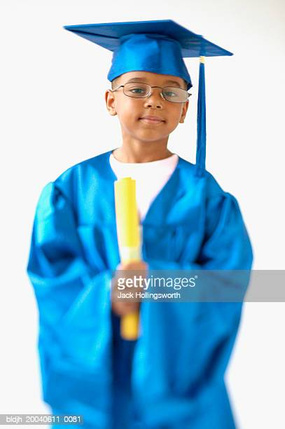 Portrait of a young boy wearing a graduation gown holding a diploma