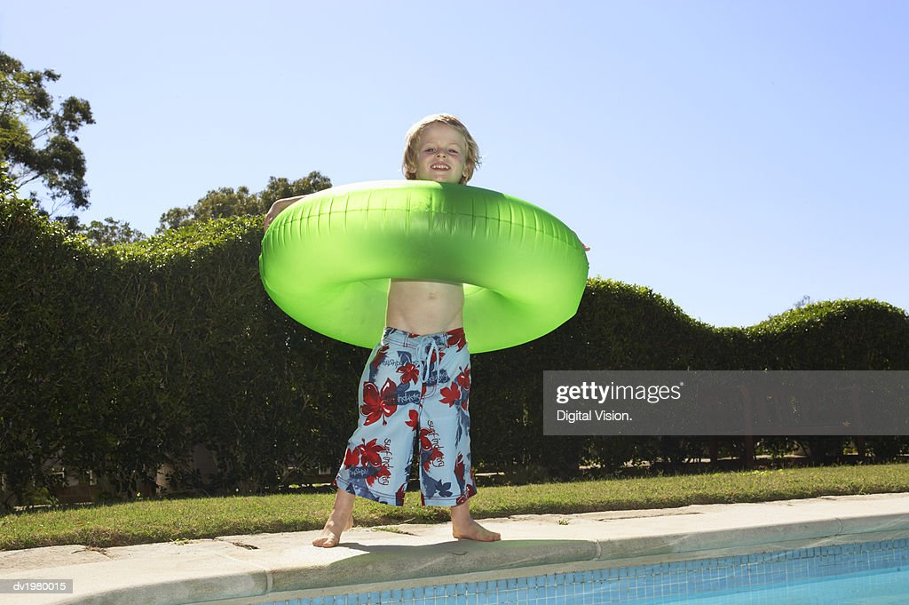 Portrait of a Young Boy Wearing a Rubber Ring Standing by a Swimming Pool : Stock Photo