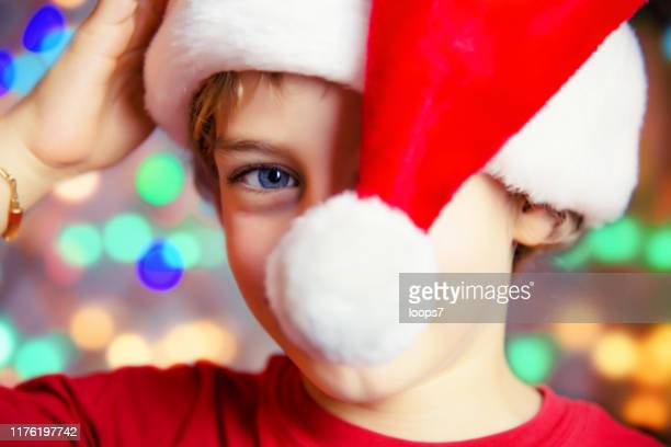 portrait of a young boy wearing santa's hat and smiling - santa face stock pictures, royalty-free photos & images