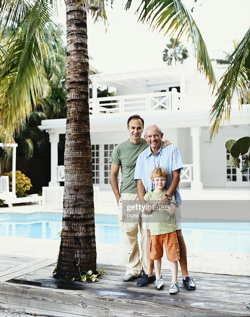 Portrait of a Young Boy With His Father and Grandfather Standing by a Swimming Pool : Stock Photo