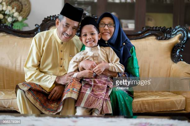 portrait of a young boy with his grandparents - hari raya stock pictures, royalty-free photos & images