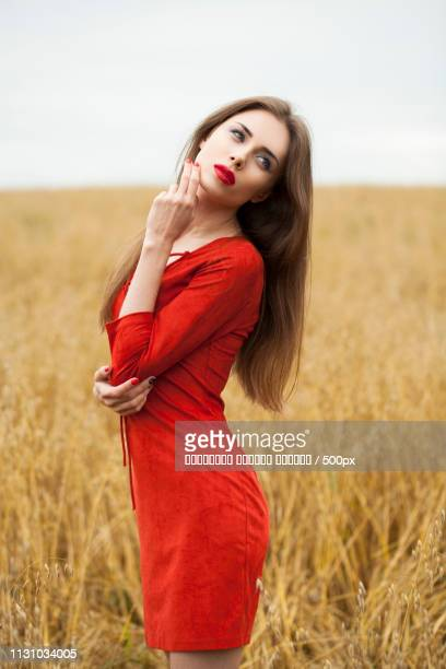 Portrait Of A Young Brunette Woman In Red Dress