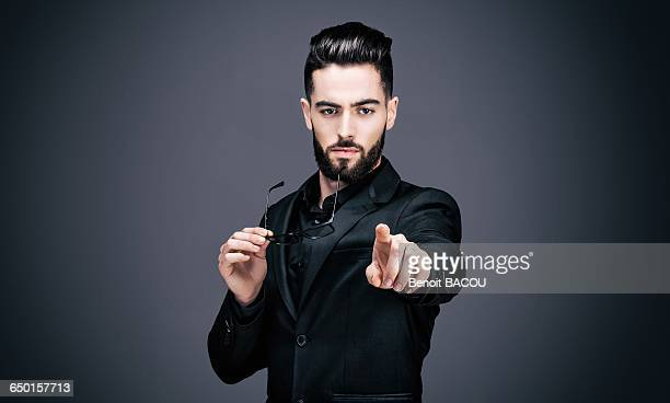 portrait of a young businessman, a pair of glasses in one hand, pointing the lens - charming stock pictures, royalty-free photos & images