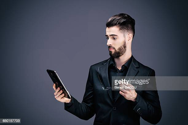 Portrait of a young businessman caught holding a touch pad in his hands
