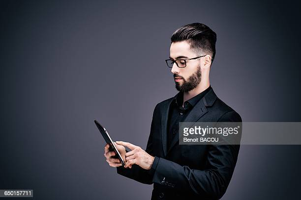 Portrait of a young businessman holding a touch pad in his hands
