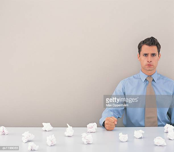 Portrait of a Young Businessman Making a Fist Sitting at a Table Surrounded by a Large Group of Paper Balls