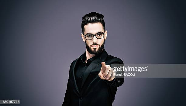 Portrait of a young businessman pointing to the lens