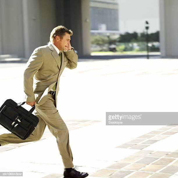 portrait of a young businessman running with a briefcase while talking on a mobile phone