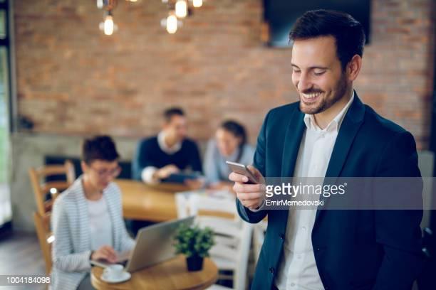 portrait d'un jeune entrepreneur tapant message texte - décontracté chic photos et images de collection