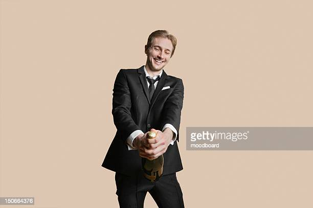 Portrait of a young businessman uncorking champagne over colored background
