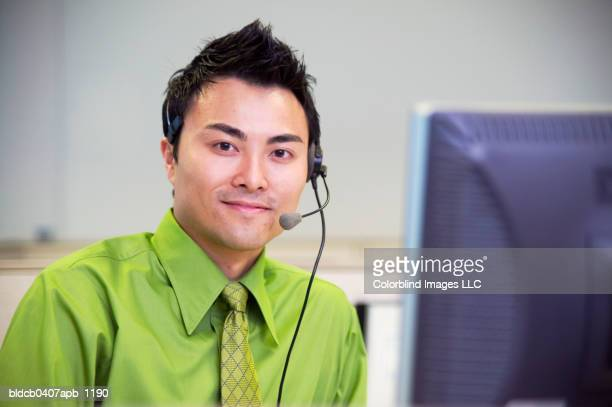 Portrait of a young businessman wearing a headset sitting in front of a computer screen