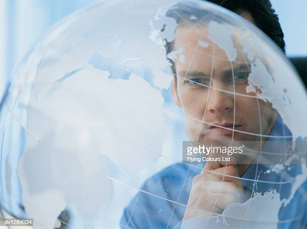 Portrait of a Young Businessman With His Hand on  His Chin Looking at a Desktop Globe