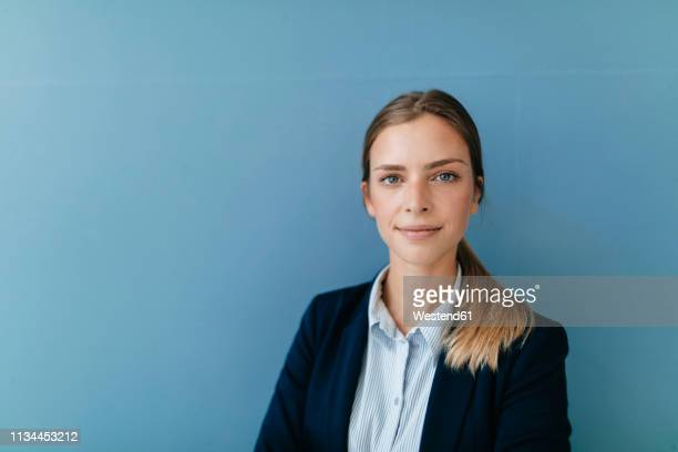 portrait of a young businesswoman against blue background - blauer hintergrund stock-fotos und bilder