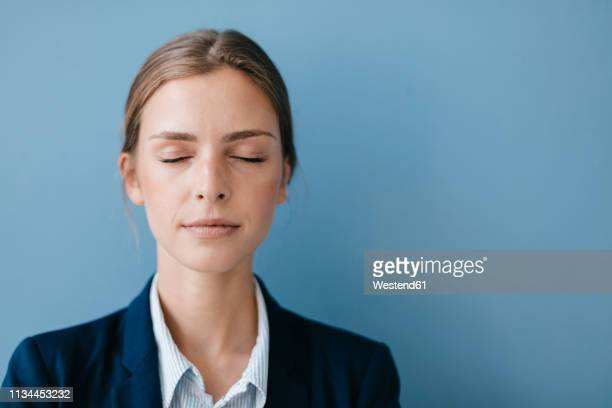 portrait of a young businesswoman against blue background, relaxing with eyes closed - eyes closed stock pictures, royalty-free photos & images
