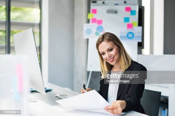 A portrait of a young businesswoman in the office sitting at the desk, working.