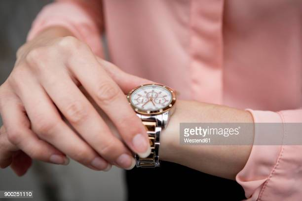 portrait of a young businesswoman looking on her wristwatch - wrist watch stock pictures, royalty-free photos & images