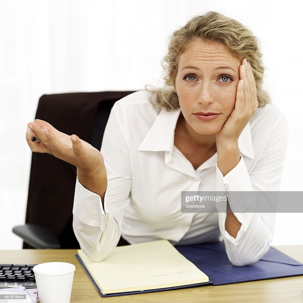 portrait of a young businesswoman sitting baffled at her desk : Stock Photo