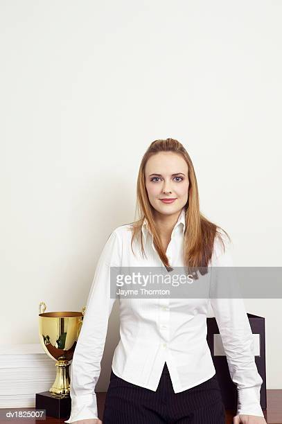 Portrait of a Young Businesswoman Standing by a Shelf With a Trophy