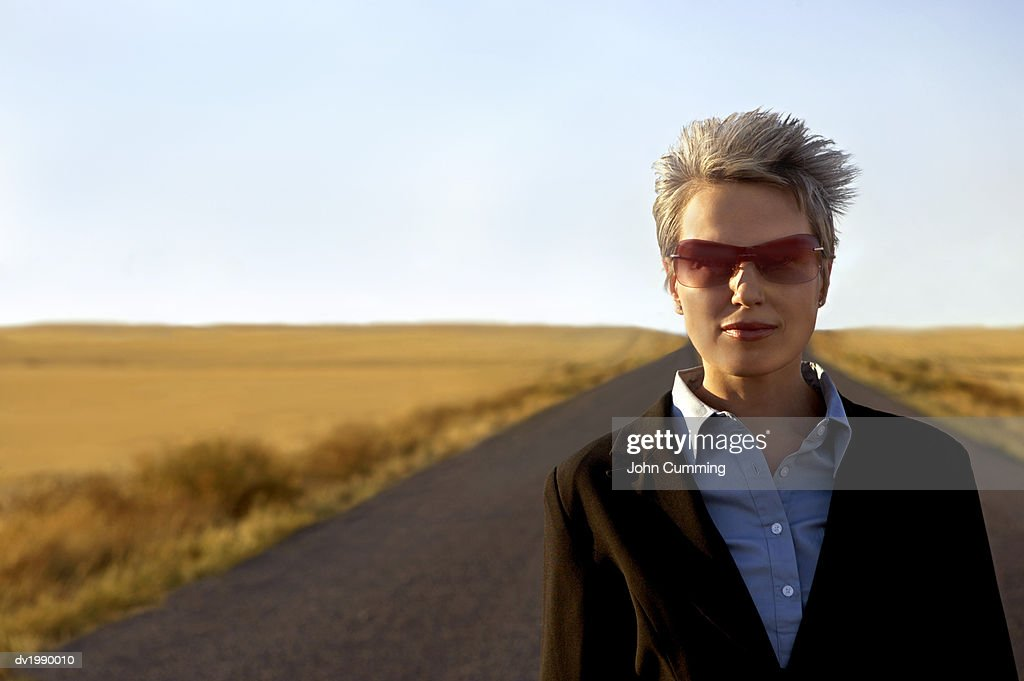 Portrait of a Young Businesswoman Wearing Sunglasses Standing on a Remote Road : Stock Photo