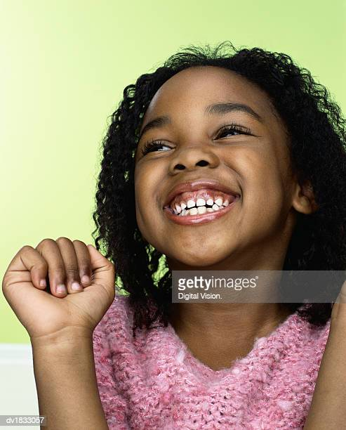 Portrait of a Young, Carefree Girl Looking Upwards and Laughing