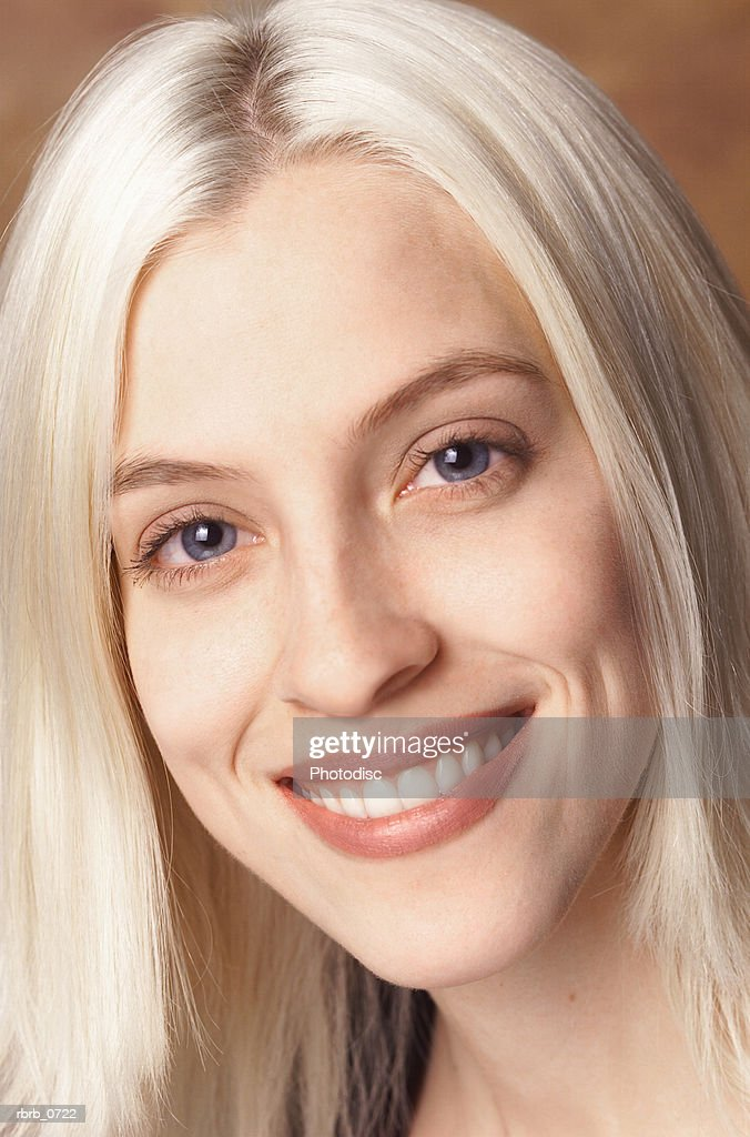 portrait of a young caucasian blonde woman as she smiles at the camera : Stockfoto