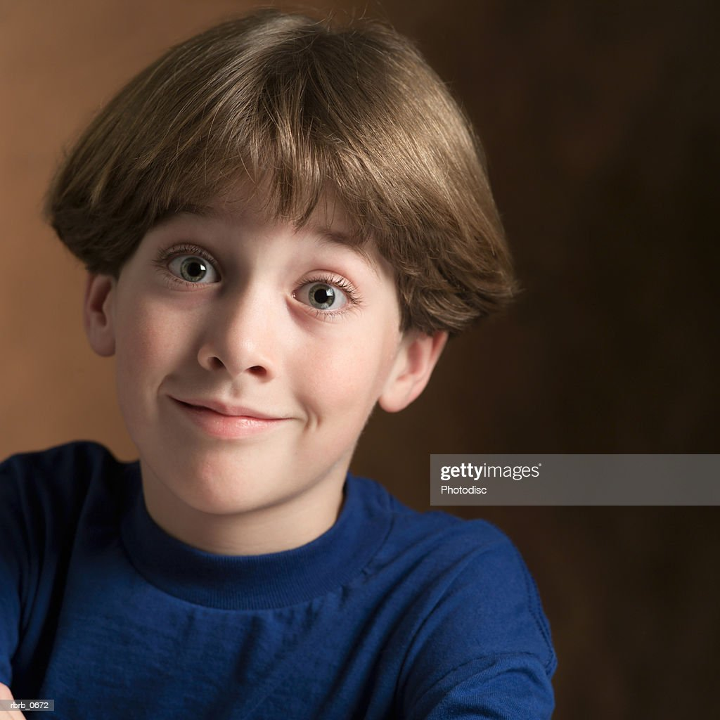 portrait of a young caucasian boy in a blue shirt as he flashes a silly grin : Stock Photo