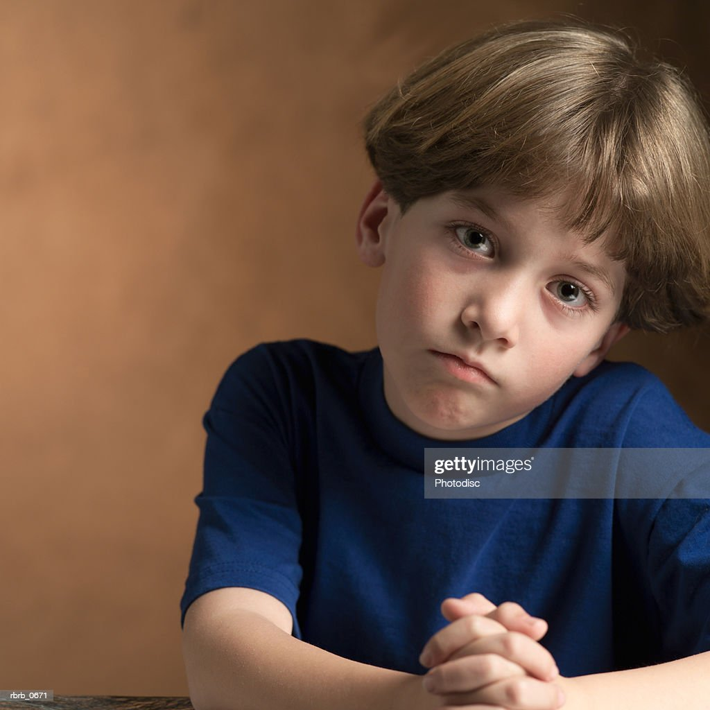 portrait of a young caucasian boy in a blue shirt as he makes a sad face : Stockfoto