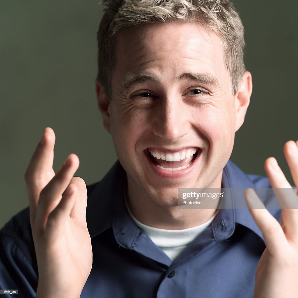 portrait of a young caucasian man in a blue shirt as he gestures with his hands and laughs : Stock Photo