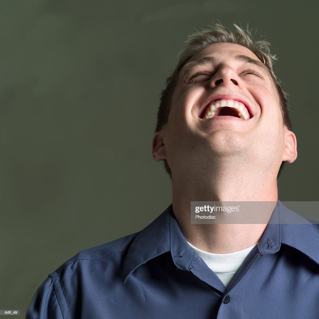 portrait of a young caucasian man in a blue shirt as he throws his head back and laughs : Foto de stock
