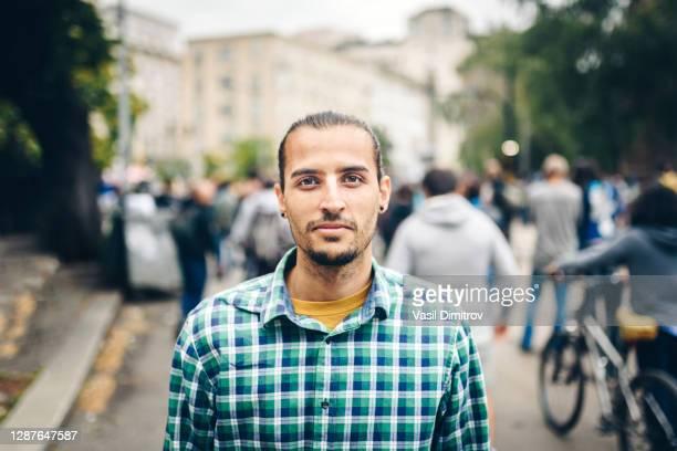 portret van een jonge kaukasische / gemengde rasmens in de stad. jonge mens die rechtstreeks de camera bekijkt. - human arm stockfoto's en -beelden